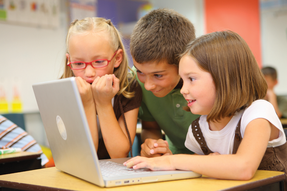 Three kids playing on computer